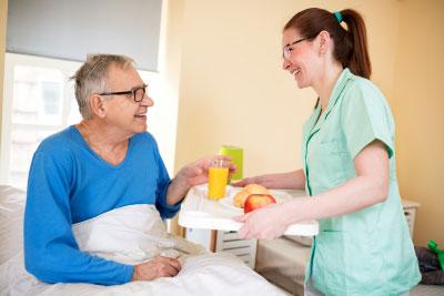 Smiling happy senior patient waiting breakfast at nursing home, care elderly people