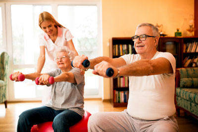 Young nurse at nursing home helps senior people to doing exercises