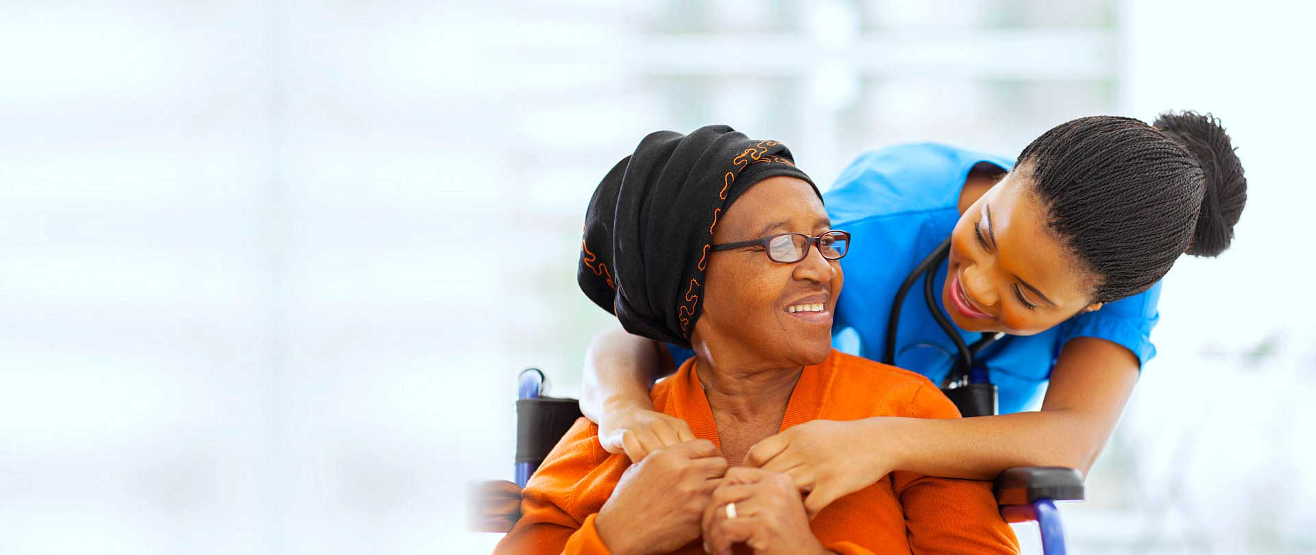 photo of a senior woman on a wheelchair with her caregiver