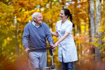 Nurse helping elderly senior man. Senior men using a walker with caregiver outdoor