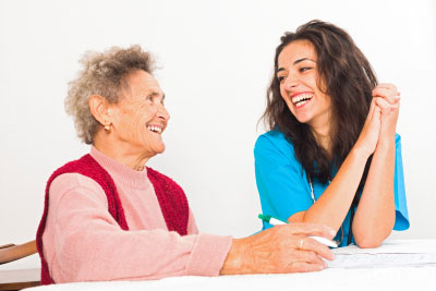 Happy elderly lady laughing with kind nurse carer working in homecare